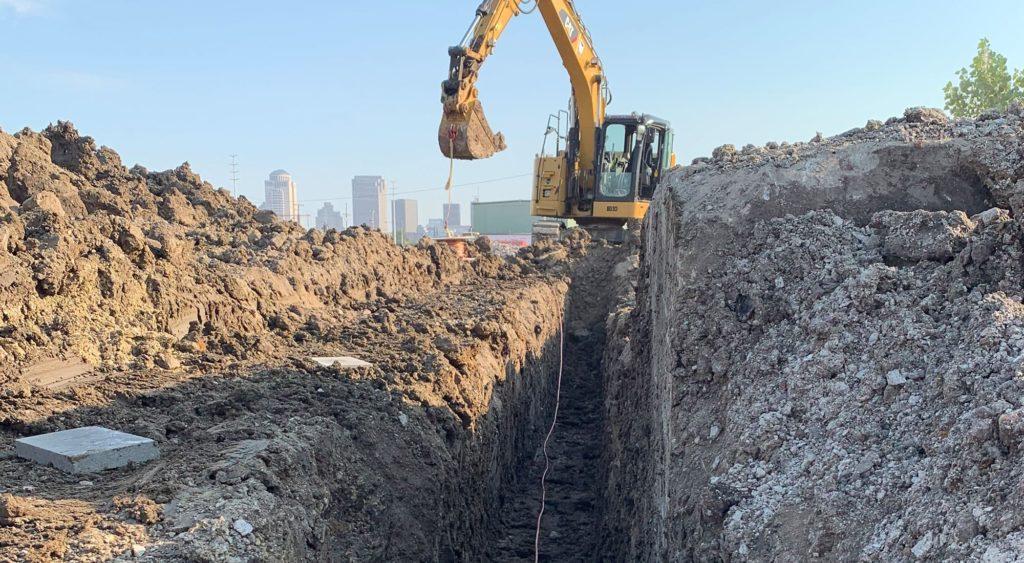 Excavator digging trench.